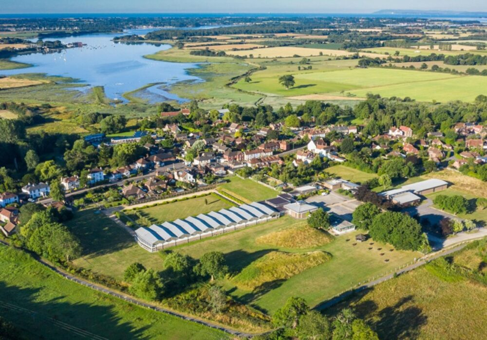 A photo showing an aerial view of Fishbourne near Chichester, with the Roman Palace in the foreground and the harbour in the background