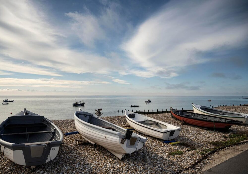 An image of Selsey beach with boats in the foreground