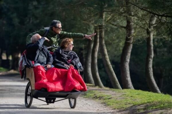 An image showing a couple being piloted on a trishaw ride